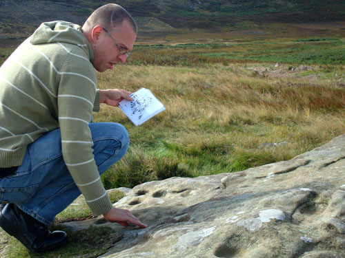 Figure 7. Participant exploring the carving through touch and visual material, Lordenshaw site visit (Rothbury, Workshop 3)