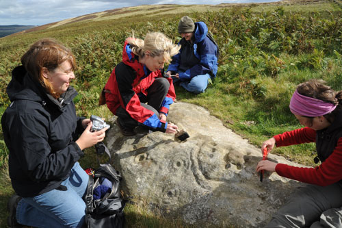 Figure 8. Participants engaging with rock art, Lordenshaw site visit (Rothbury, Workshop 3)